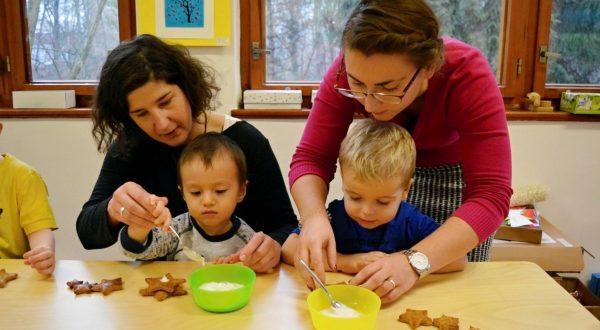 Nejmenší děti za pomoci dospělých vrábějí vánoční ozdoby