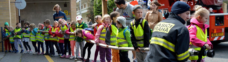 Děti drží hasišskou hadici