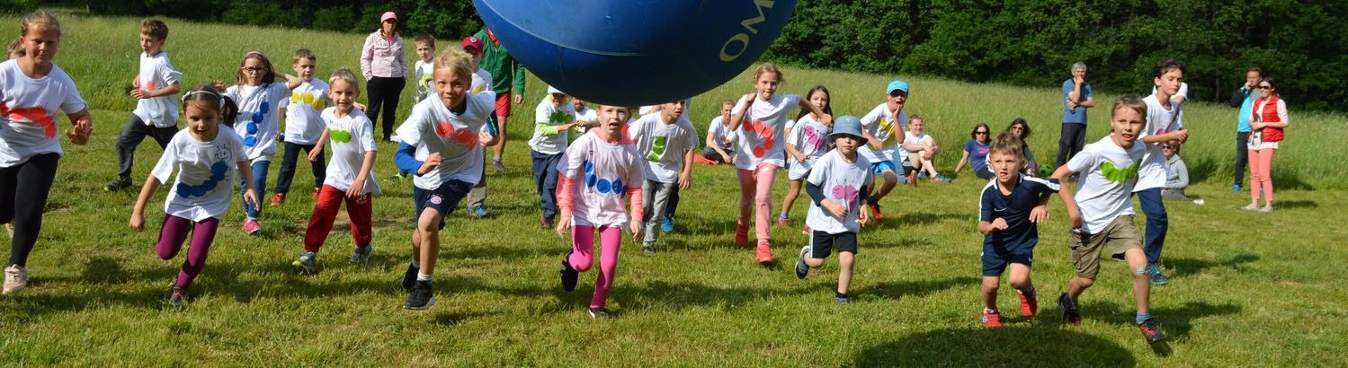 Děti běží za kinbalovým míčem