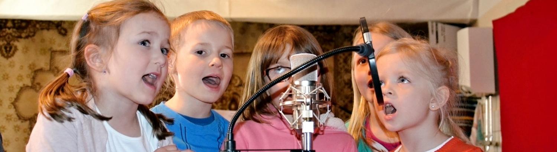 Děti spívají ve studiu na mikrofon